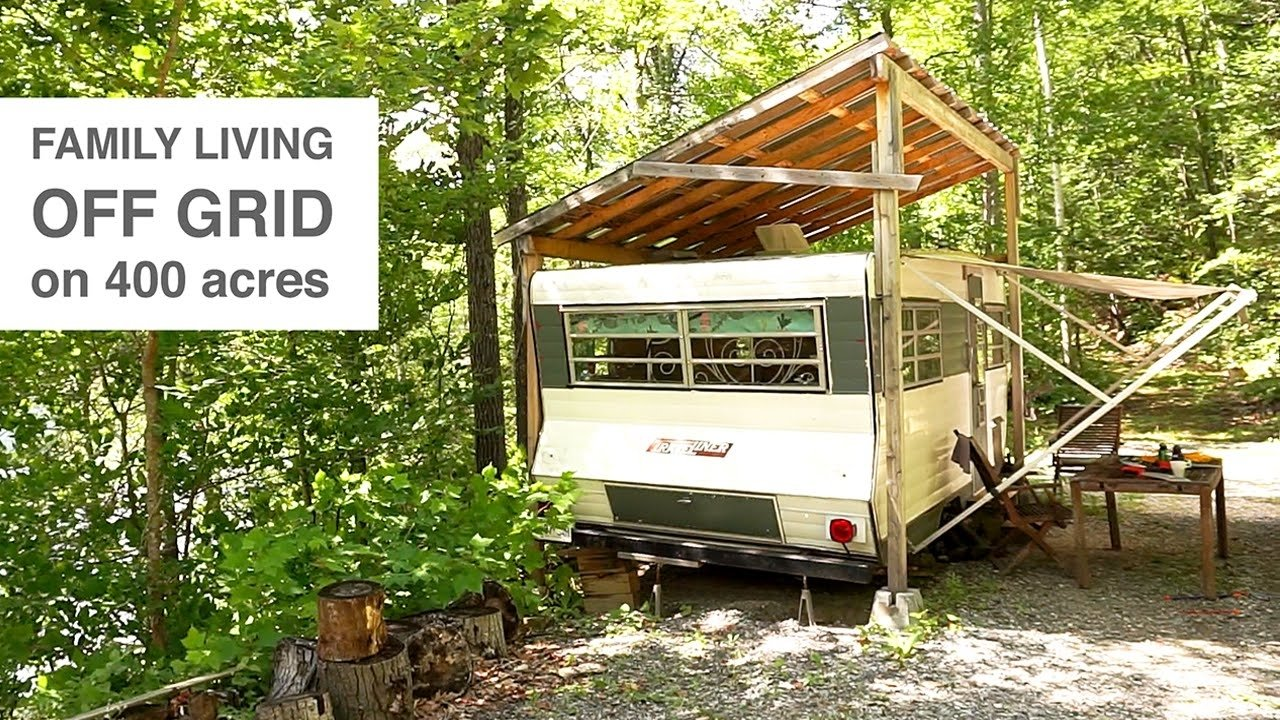 family living off grid in camper trailer & tree house style studio