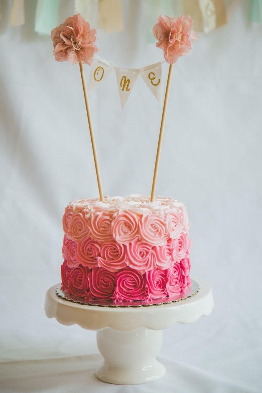 10 Unique First Birthday Smash Cake Ideas pastel flores tonos de rosas banderines dorados con pompones 1st