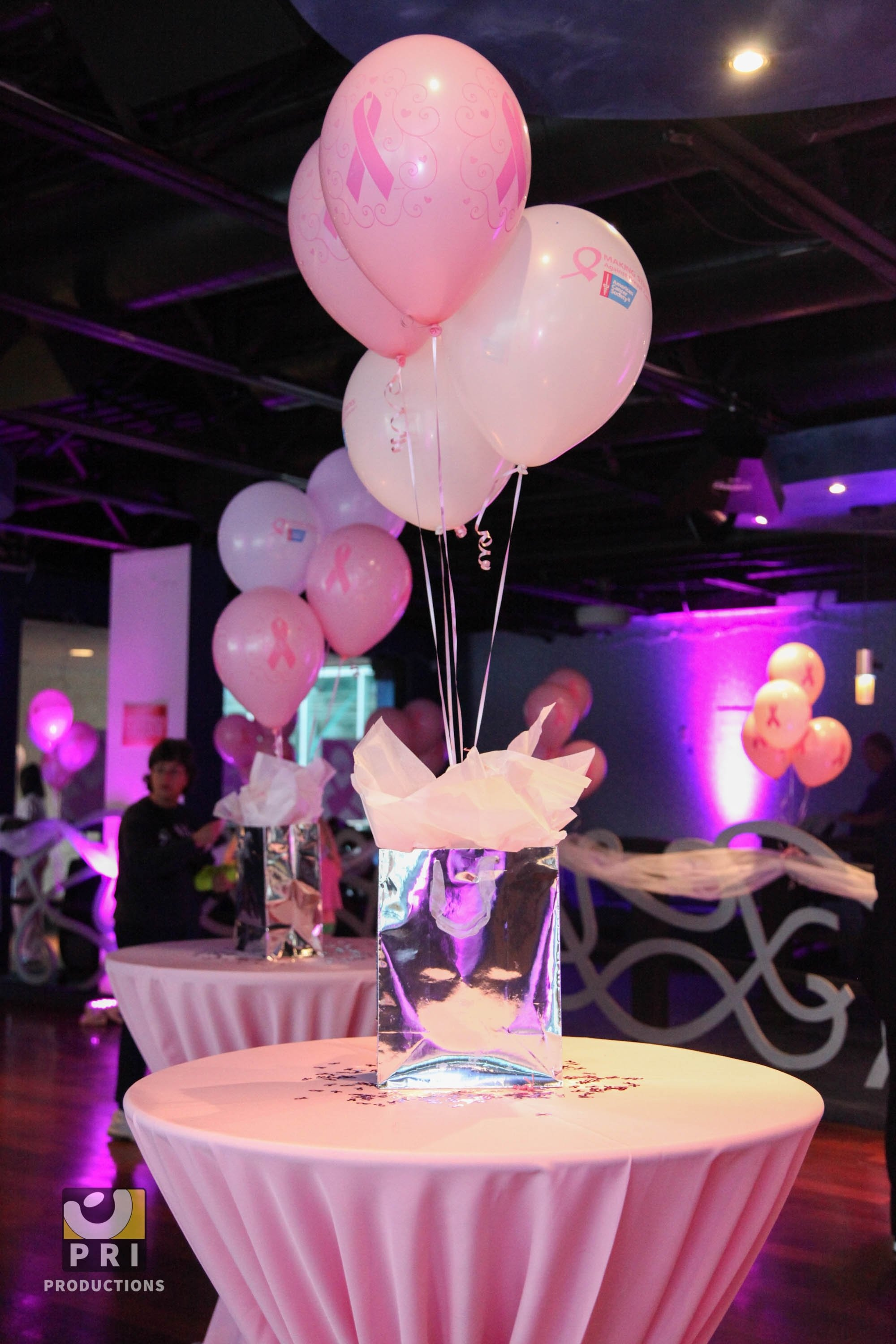 10 Fantastic Fundraising Ideas For Breast Cancer pink balloon and gift bag centerpiece with matching table linens for 2020