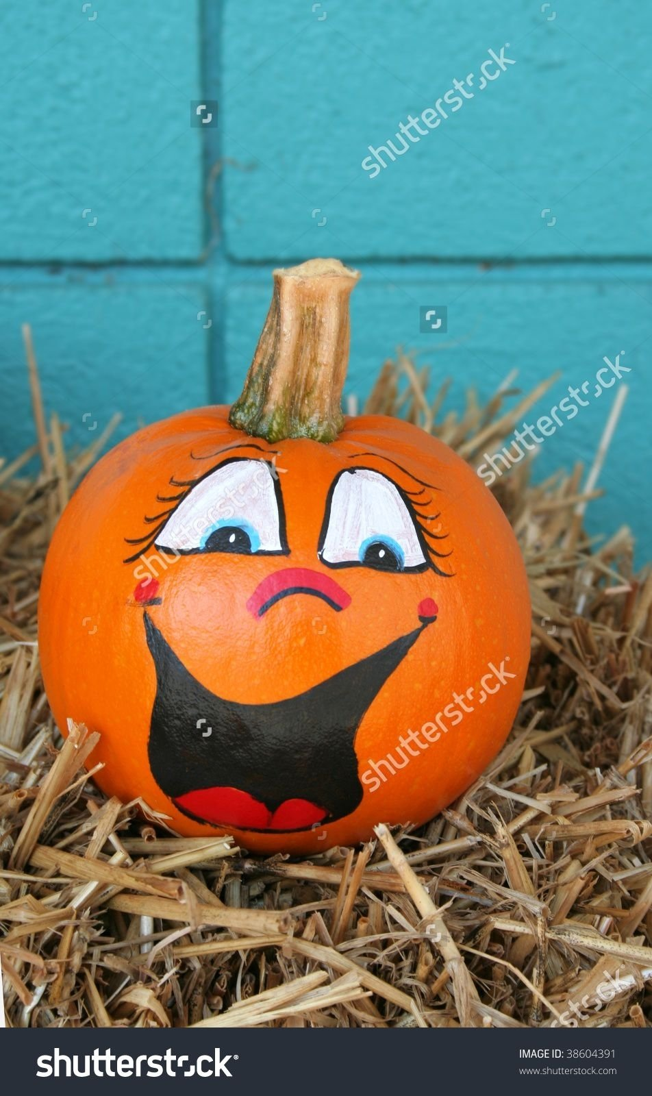10 Attractive Pumpkin Decorating Ideas Without Carving stock photo smiling pumpkin with a painted face and sitting on hay 2020